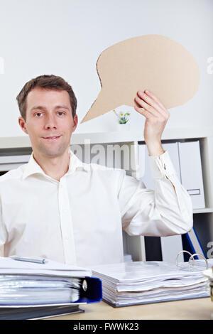 Smiling business man holding empty comic speech bubble - Stock Photo