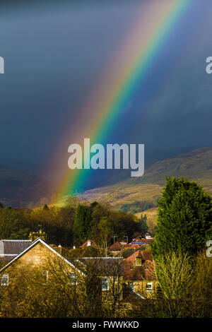 Rainbow over Scottish Village of Lennoxtown showing village church and Campsies in background - Stock Photo