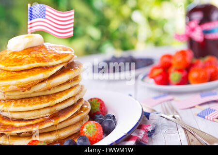 A stack of homemade pancakes with fresh fruit, butter and syrup. - Stock Photo