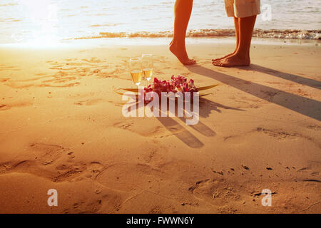 wedding on the beach, feet of romantic couple and two glasses of champagne at sunset - Stock Photo