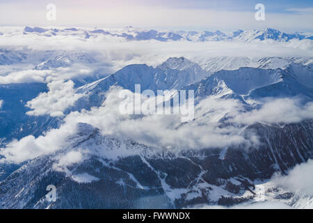 Alps, panoramic view of winter mountains with clouds above seen from Punta Helbronner - Stock Photo