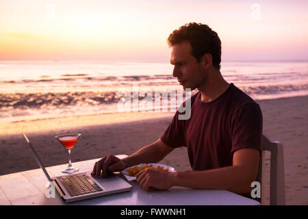 man with laptop in beach restaurant at sunset - Stock Photo