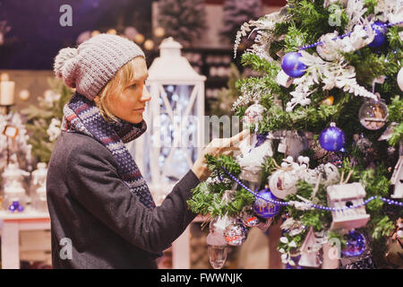 people at christmas market, woman choosing festive decoration in the shop - Stock Photo