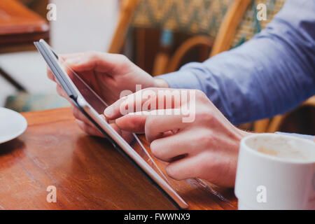 checking email on touchpad, close up of hands using digital tablet in cafe - Stock Photo