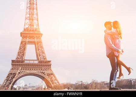 love in the most romantic city - Paris, young couple at Eiffel Tower and vanilla sky - Stock Photo