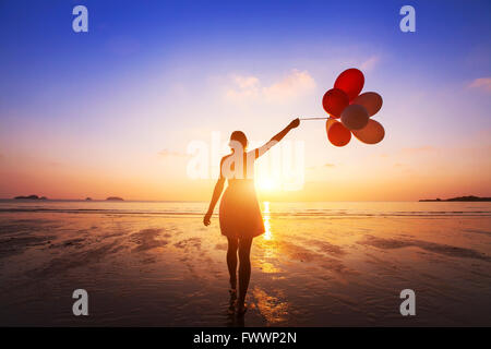 happiness concept, positive emotions, happy girl with multicolored balloons enjoying summer beach at sunset - Stock Photo