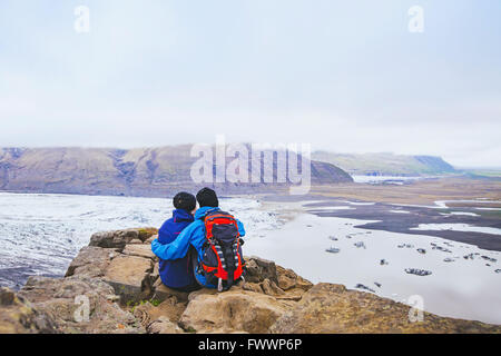 couple of hikers travel in Iceland, two backpackers enjoying view of glacier and mountain landscape - Stock Photo