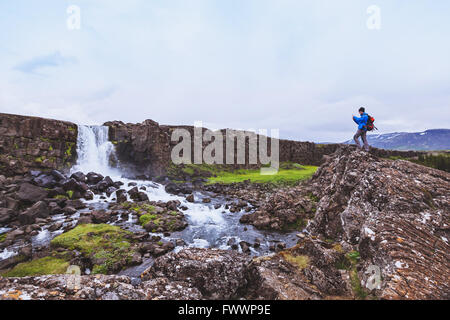 backpacker traveler taking photo of waterfall with mobile phone - Stock Photo