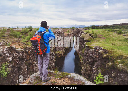 nature photographer, hiker with backpack taking photo of beautiful landscape in Iceland national park Thingvellir - Stock Photo