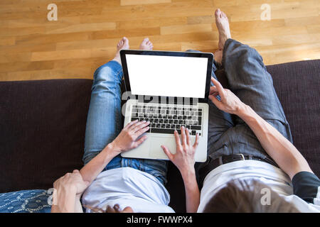 young couple using internet on laptop with empty blank screen at home, top view, buy or rent online concept - Stock Photo