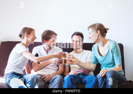 group of friends cheering at home, happy young smiling people with drinks, copyspace - Stock Photo