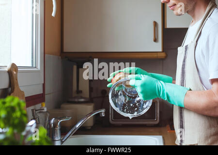 man washing dishes in the kitchen sink at home, close up of hands with sponge and soap, housework - Stock Photo