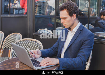 young handsome buisnessman using internet on mobile phone while sitting in open street cafe - Stock Photo