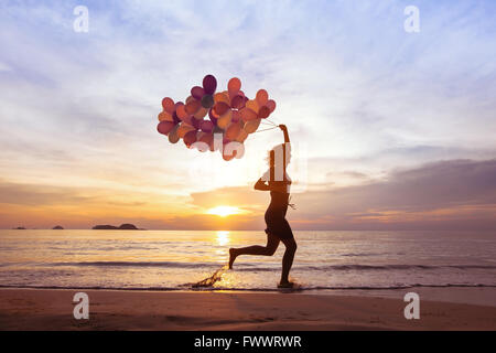 happiness concept, psychology of happy people, young woman running with multicolored balloons on the beach - Stock Photo
