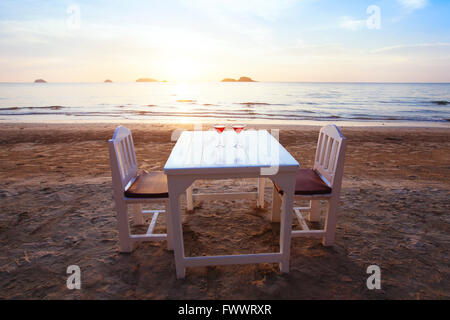 two cocktails on the table in luxury beach restaurant at sunset - Stock Photo