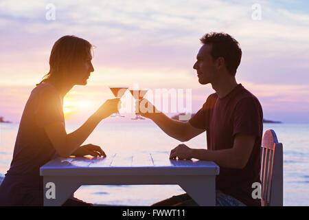 couple in restaurant, drinking cocktails on the beach at sunset
