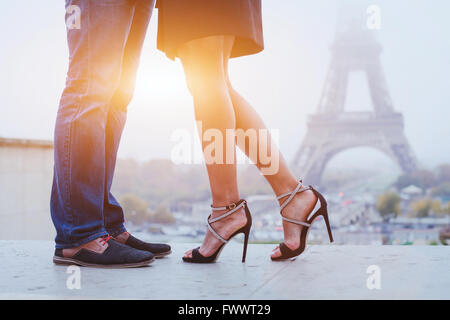romantic holidays in Paris, feet of couple kissing near Eiffel tower - Stock Photo