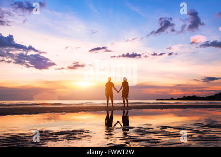 romantic couple on the beach at sunset, silhouettes of man and woman together - Stock Photo