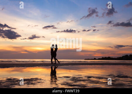silhouette of couple on sunset beach, beautiful background about love and relationships, man and woman - Stock Photo