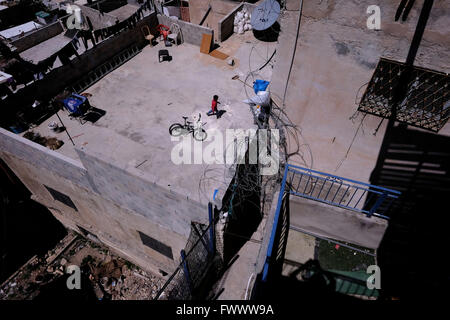 Jerusalem, Israel. 7th April, 2016. A Palestinian kid is seen from the rooftop of a building that Jewish settlers - Stock Photo