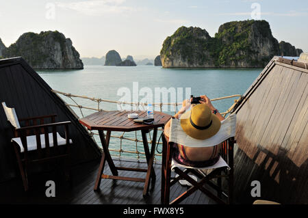 Young caucasian woman sitting on a chair takes a picture in Bai Tu Long area of Ha Long Bay from the deck of a junk, - Stock Photo