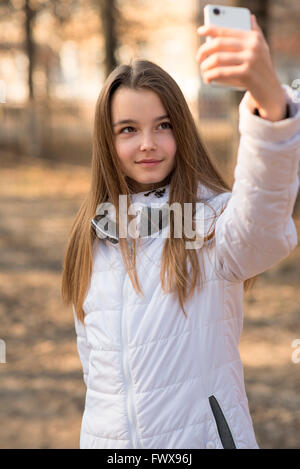 Beautiful girl takes a picture of the self, smiling - Stock Photo