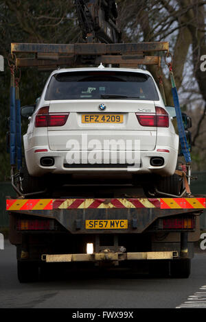 An illegally parked BMW X5 4x4 car being removed by parking wardens on a flatbed truck - Stock Photo
