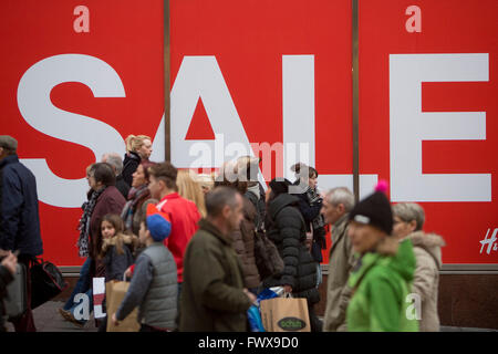 A group of shoppers walk under a giant sale sign in Glasgow's Buchanan Street. - Stock Photo