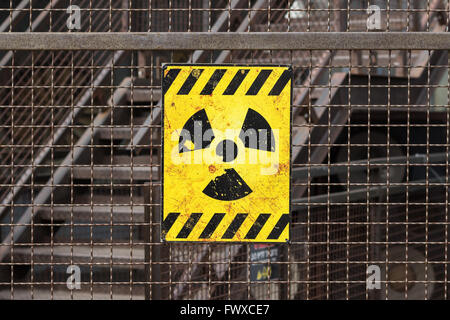 yellow radioactive warning sign on rusty fence - Stock Photo
