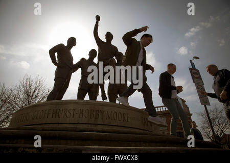 Fans jumping down from the statue of Bobby Moore with the World Cup near the Boleyn Ground before West Ham United - Stock Photo