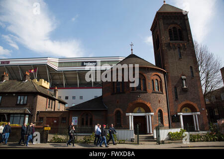 Fans walking along Green Street past the the Our Lady of Compassion Catholic church outside the Boleyn Ground before - Stock Photo