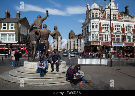Fans sitting at the World Cup statue on Barking Road, with the Boleyn pub, a regular gathering place for home fans, - Stock Photo