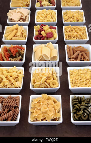 Pasta dried food varieties in white square porcelain bowls - Stock Photo