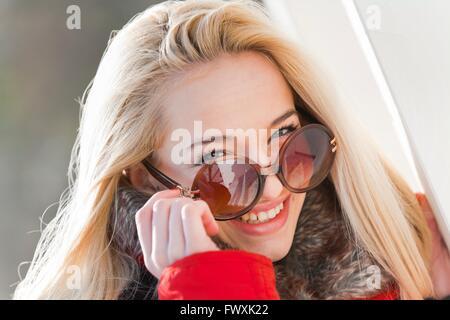 Teenager girl smile portrait happy looking peek peeking above glasses sunglasses teaser teasing blonde long hair - Stock Photo
