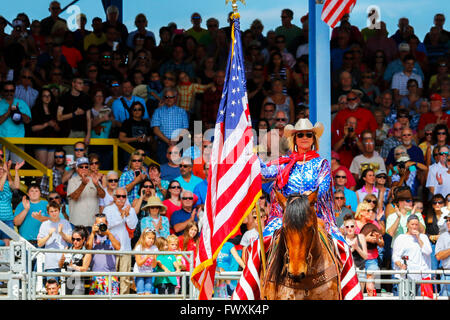 Woman on horseback, dressed in America colours and carrying the Stars and Stripes, American flag, Arcadia Rodeo, - Stock Photo