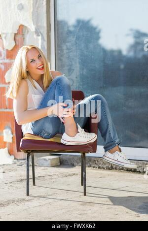 Girl next door denims sneakers leg on chair tucked laughing at camera outdoors loud chirp yell ordinary people attractive - Stock Photo