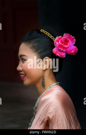 A beautiful Thai woman with a flower in her hair and wearing traditional dress - Stock Photo