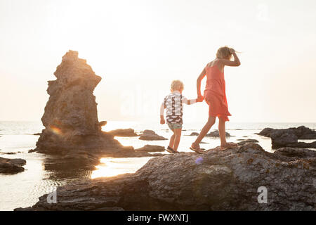 Sweden, Gotland, Faro, Gamle hamn, Girl (8-9) walking with brother (2-3) on coastal rocks - Stock Photo