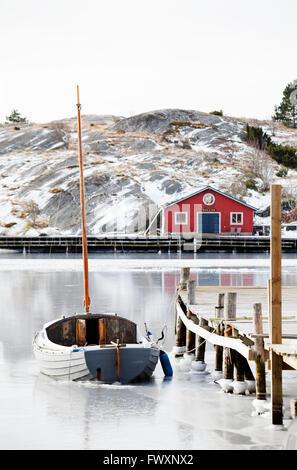 Sweden, Bohuslan, Orust, Mollosund, Boat by wooden jetty in winter - Stock Photo