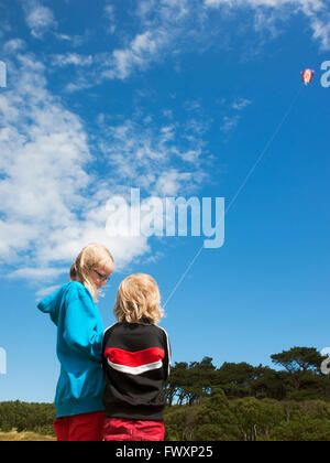 Sweden, Skane, Nyhamnslage, Two sisters (6-7, 10-11) flying kite - Stock Photo