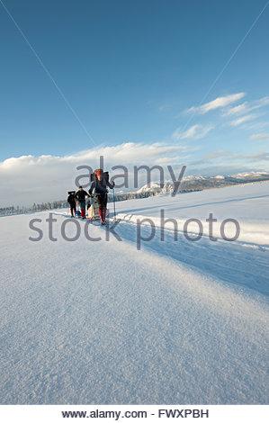 Sweden, Lappland, Jokkmokk, Three men walking in snow - Stock Photo