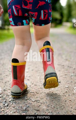 Sweden, Little boy (2-3) walking in rubber boots - Stock Photo