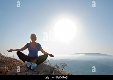 Spain, Alicante, Cocentaina, Mature woman sitting cross-legged on rocks and meditating - Stock Photo