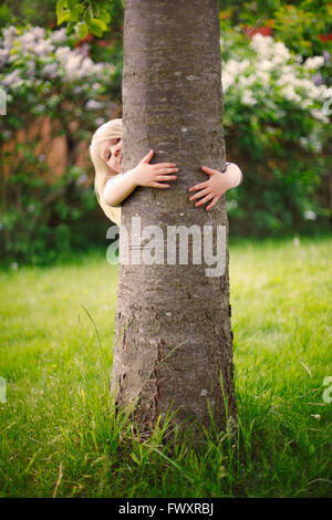 Sweden, Bohuslan, Tjorn, Girl (4-5) hiding behind tree - Stock Photo