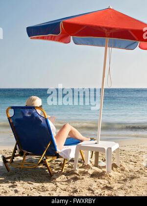 Greece, Karpathos, Woman sunbathing and reading book at beach - Stock Photo