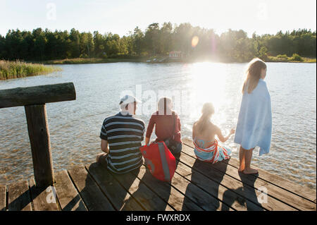 Sweden, Vastra Gotaland, Kallandso, Family with two children (6-7, 12-13) on pier - Stock Photo