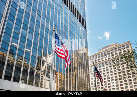 USA, New York State, New York City, Manhattan, American flags with skyscrapers in background - Stock Photo