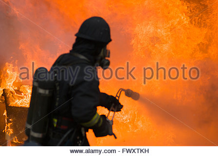 Sweden, Sodermanland, Firefighter spraying water to stop fire - Stock Photo