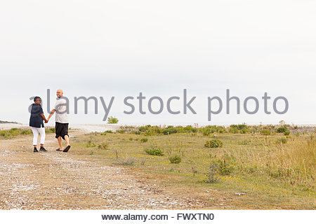 Sweden, Gotland, Furillen, Mid adult couple holding hands and walking along footpath - Stock Photo