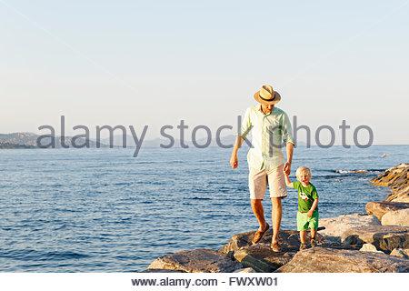 France, Provence-Alpes-Cote d´Azur, Saint Tropez, Man walking with son along rocky coast - Stock Photo